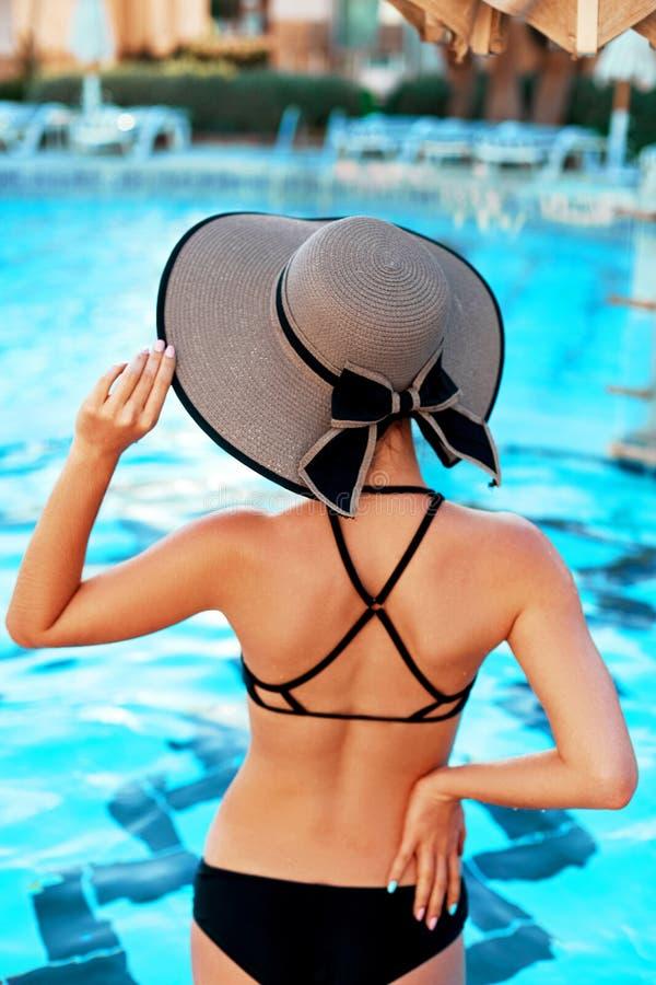 Elegante sexy Frau im Bikini auf dem sonnen-gebr?unten d?nnen und formsch?nen K?rper wirft nahe dem Swimmingpool auf lizenzfreies stockfoto