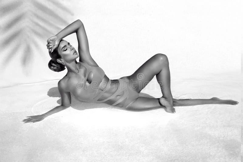 Elegante sexy Frau im erstaunlichen Bikini auf dem sonnen-gebräunten dünnen und formschönen Körper wirft nahe dem Swimmingpool au stockfotografie