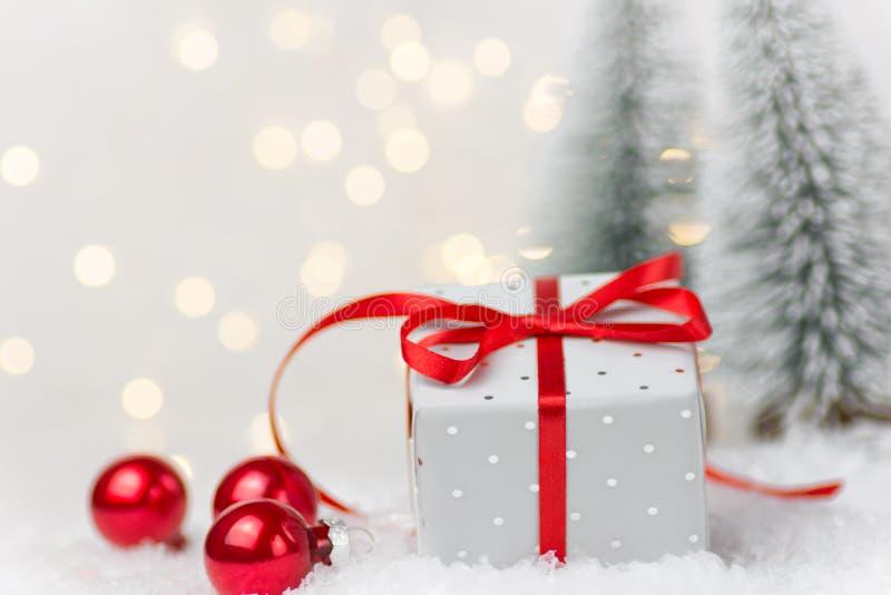 Elegante silberne Geschenkbox gebunden mit roter Seidenbandbogen-Winterszene im Wald mit Tannenbaumflitter im Schnee Weihnachtsne stockfotografie