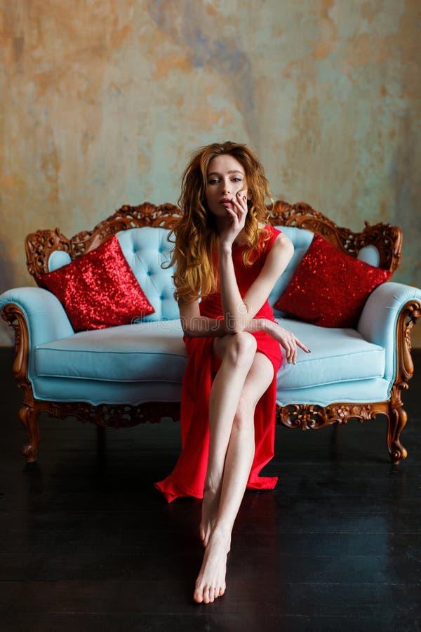 Elegante sinnliche junge Brunettefrau im roten Kleid, das auf ledernem Sofa sitzt und Kamera betrachtet stockbilder