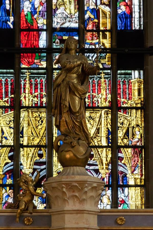 Elegante Statue in der Kirche mit Buntglas stockfotos