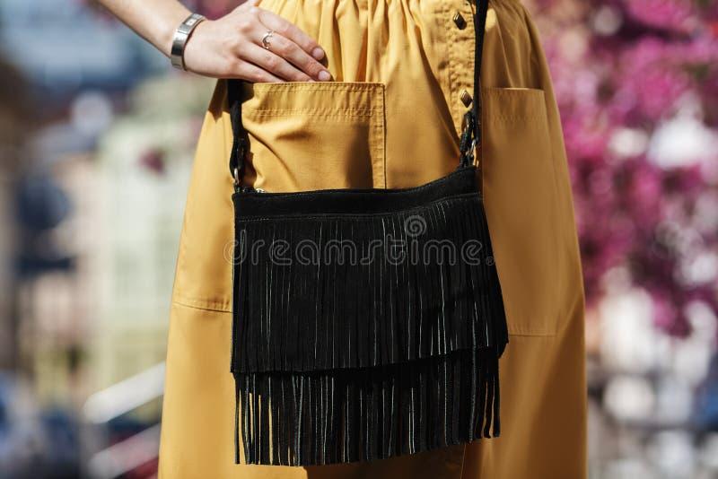 Elegante uitrusting Close-up van de kleine zwarte suèdezak met rand Bohostijl Modieus meisje op de straat wijfje stock afbeelding