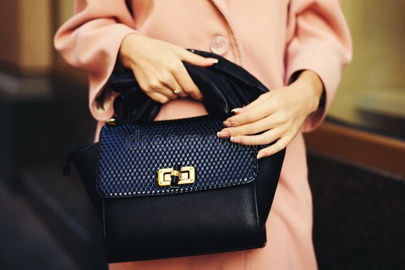 Elegante uitrusting Close-up van zwarte de handtas in hand modieuze vrouw van de leerzak Modieus meisje op de straat wijfje stock afbeeldingen