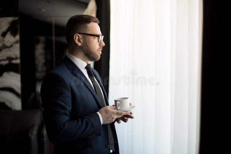 Elegante volwassen zakenman met kop van koffie stock fotografie