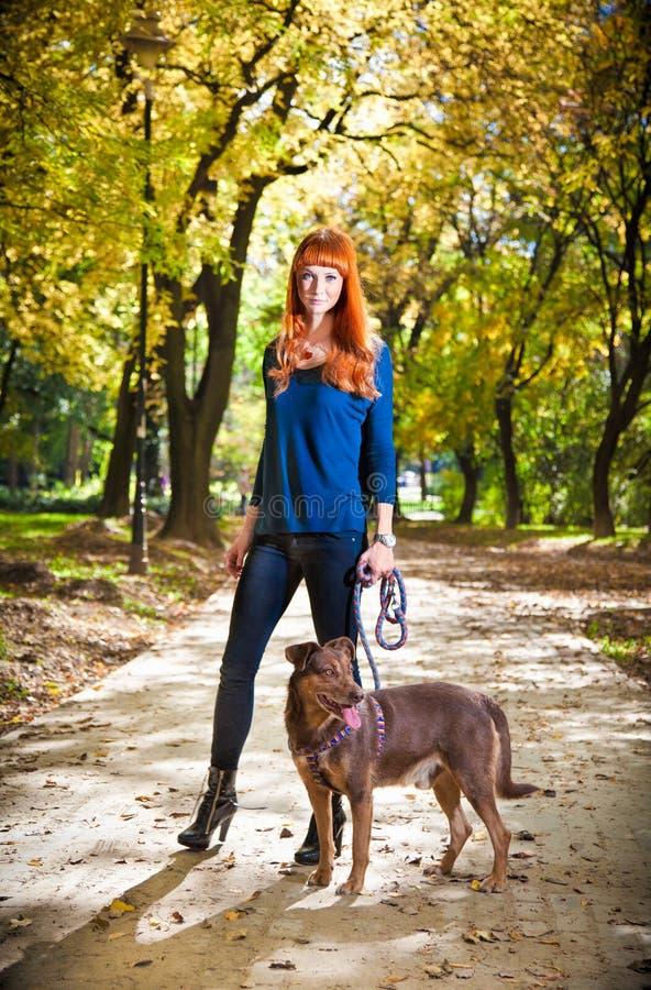 Elegante vrouw die haar grote hond in het park, Servië loopt stock afbeelding
