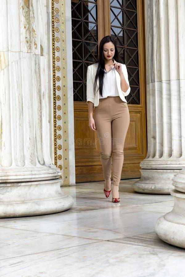 Elegante vrouw die met haar oogglazen lopen royalty-vrije stock afbeelding