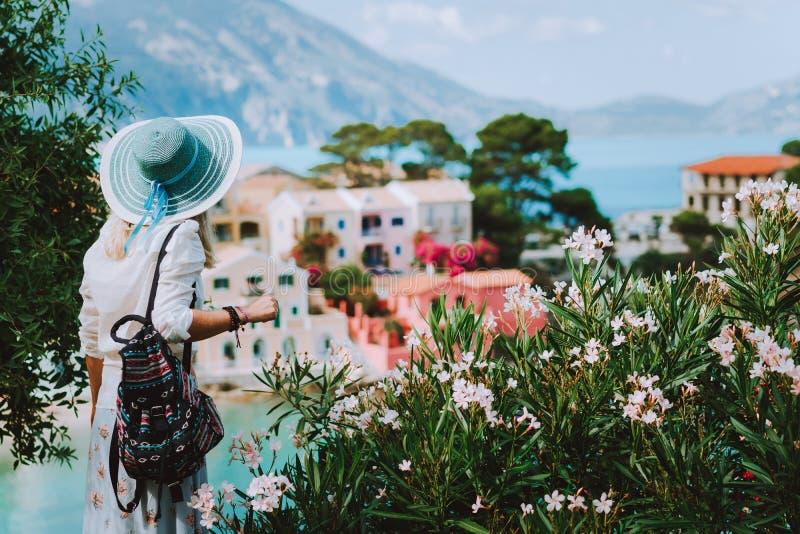 Elegante vrouw die met strohoed en witte kleren van mening van kleurrijk dorp Assos op zonnige dag genieten Het modieuze vrouweli royalty-vrije stock foto's