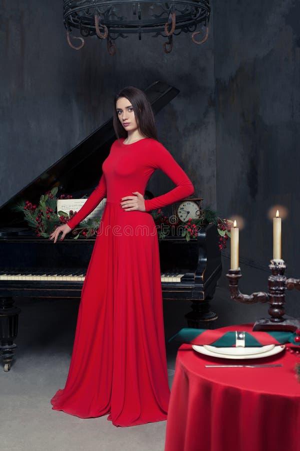 Elegante vrouw die zich bij de piano in restaurant bevinden royalty-vrije stock afbeelding