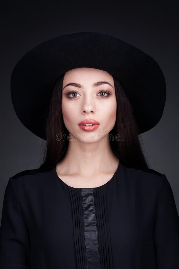 Elegante vrouw die zwarte kleding en zwarte hoed dragen royalty-vrije stock foto's