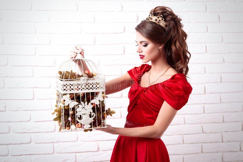Elegante vrouw in een lange rode kleding die een vogelkooi met flowe houden royalty-vrije stock fotografie