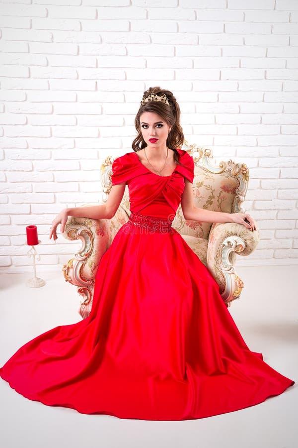 Elegante vrouw in een lange rode kledingszitting op een stoel stock afbeeldingen