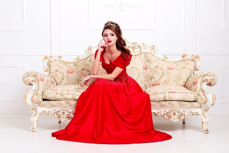 Elegante vrouw in een lange rode kledingszitting op een uitstekende bank in w royalty-vrije stock afbeeldingen