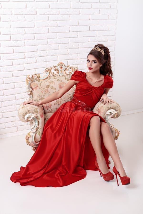 Elegante vrouw in een lange rode kledingszitting op een uitstekende stoel binnen stock foto's