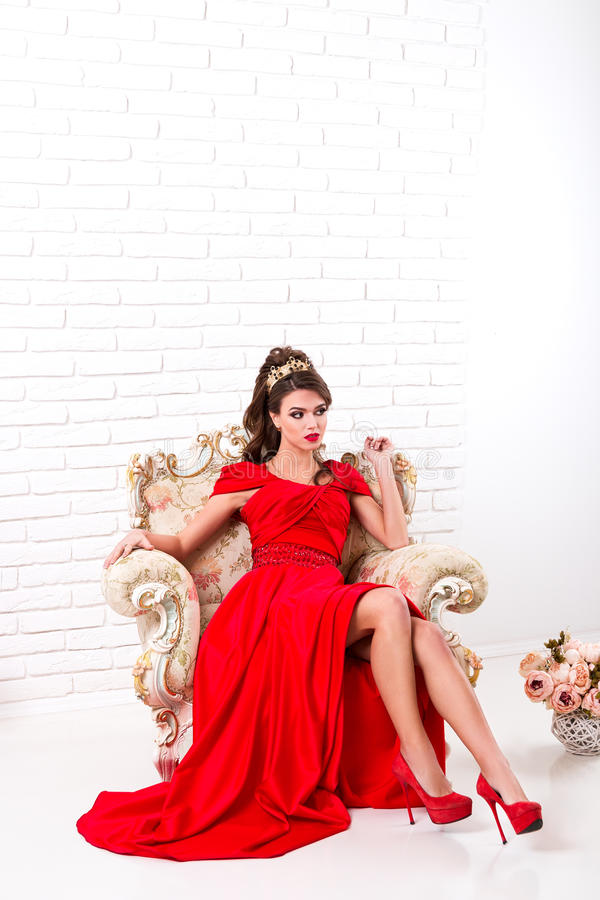 Elegante vrouw in een lange rode kledingszitting op een uitstekende stoel binnen royalty-vrije stock afbeeldingen