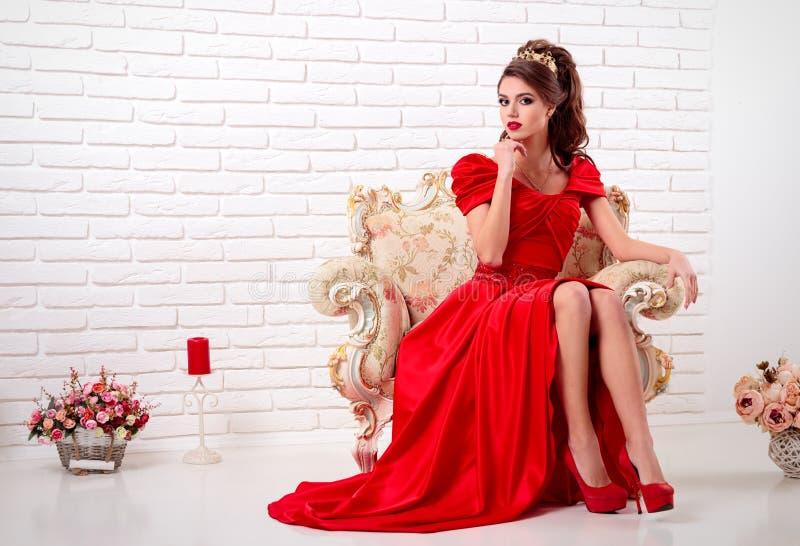 Elegante vrouw in een lange rode kledingszitting op een uitstekende stoel binnen royalty-vrije stock afbeelding