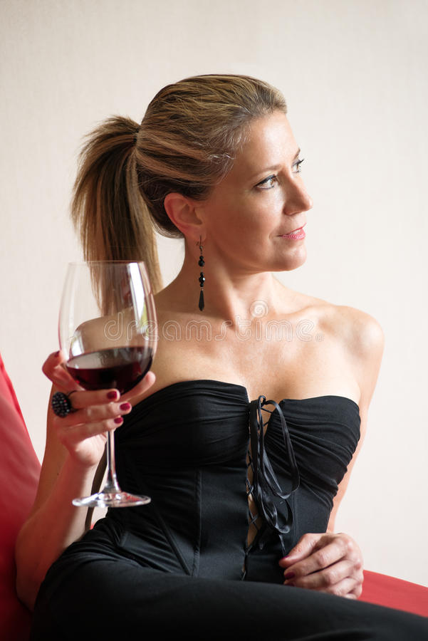 Elegante vrouw in een zwarte cocktailkleding stock fotografie