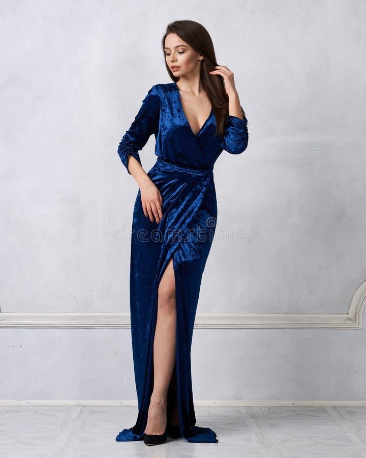 Elegante vrouw in lange lichtblauwe fluweelformele kleding stock foto