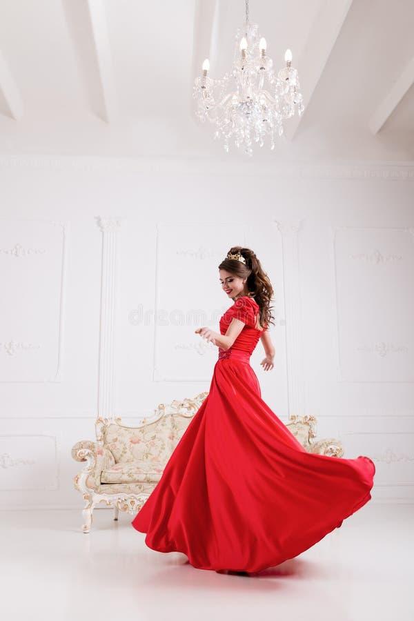 Elegante vrouw in lange rode kleding die zich in witte ruimte, kledingsfl bevinden stock fotografie
