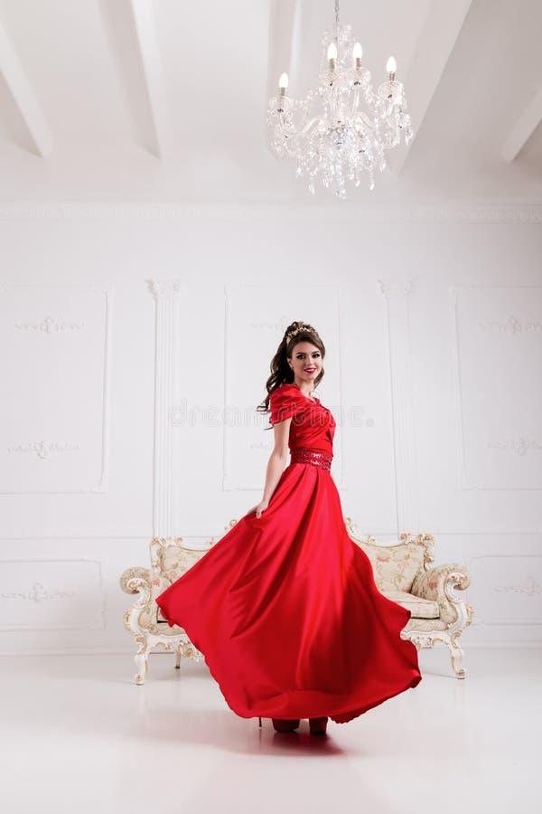 Elegante vrouw in lange rode kleding die zich in witte ruimte, kledingsfl bevinden royalty-vrije stock foto's