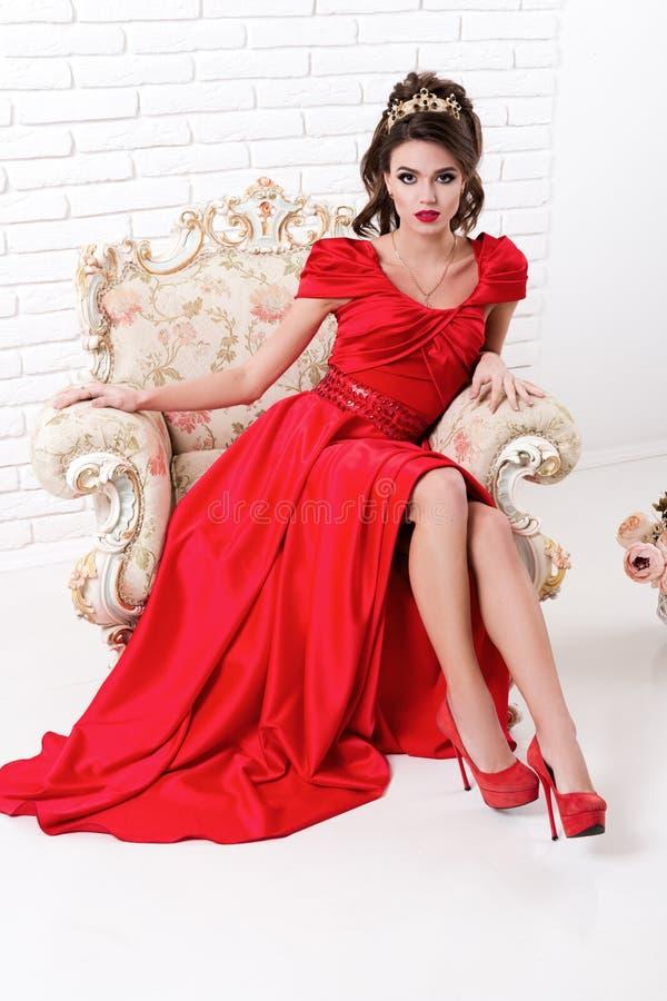 Elegante vrouw in lange rode kledingszitting op uitstekende stoel in whit stock afbeeldingen