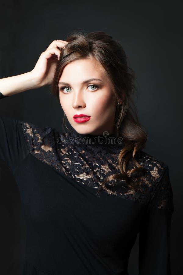 Elegante vrouw met het rode haar van de lippenmake-up op donkere achtergrond royalty-vrije stock foto