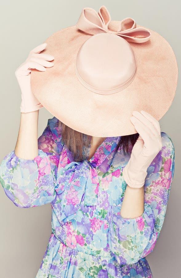Elegante vrouw met hoeden. Verbergt het gezicht. stock afbeeldingen