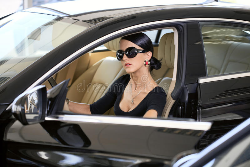 Elegante vrouw met lange benen in auto royalty-vrije stock afbeeldingen