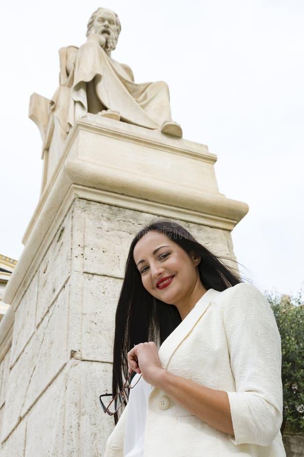 Elegante vrouw onder Socrates-standbeeld stock fotografie