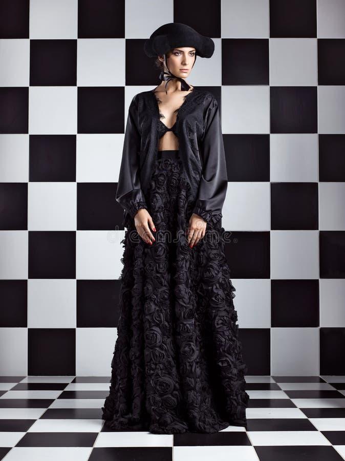 Elegante vrouw in zwarte hoed, overhemd en rok met bloemen die op schaakbord stellen stock foto