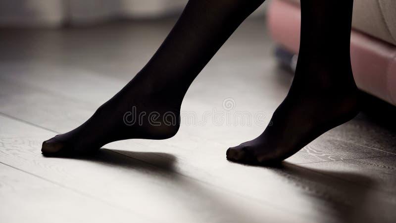 Elegante vrouwelijke benen in zwarte legging op de vloer, de stijl en de manier, kleding stock foto