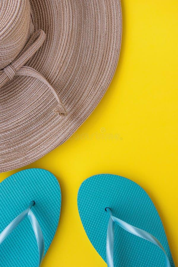 Elegante Vrouwen Straw Hat met Boog Blauwe Pantoffels bij het Gele de Kust van de Achtergrondstrandvakantie Reizen stock afbeelding