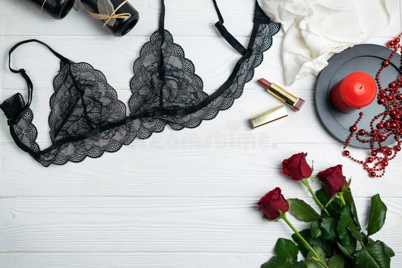 Elegante Wäschezusammensetzung der schwarzen Spitzes mit roten Rosen und Kerze stockbilder