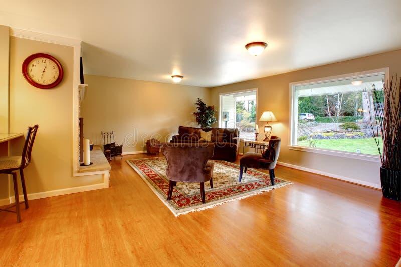 Elegante warme kleur geleverde woonkamer met brede vensters stock afbeeldingen