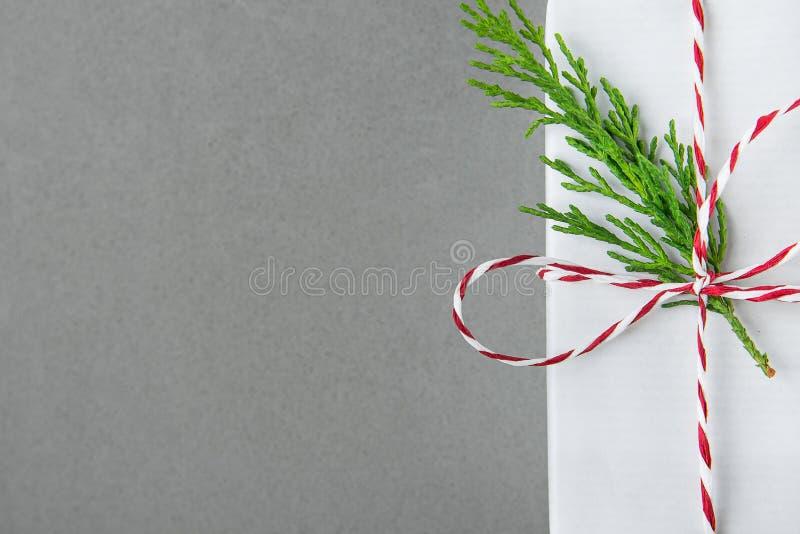 Elegante weiße Geschenkbox gebunden mit dem roten Band-Grün-Wacholderbusch-Zweig Weihnachtsneue Jahr-Geschenk-Einkaufsverkauf Gra stockfotos