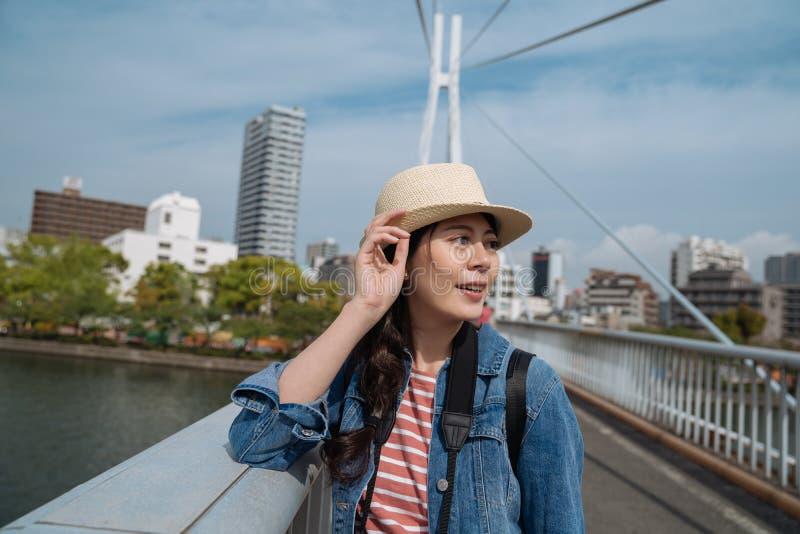 Elegante weibliche Reisendstellung auf der Brücke an einem sonnigen Tag beiseite schauend junger Tourist mit Besichtigungsosaka-S stockfotografie