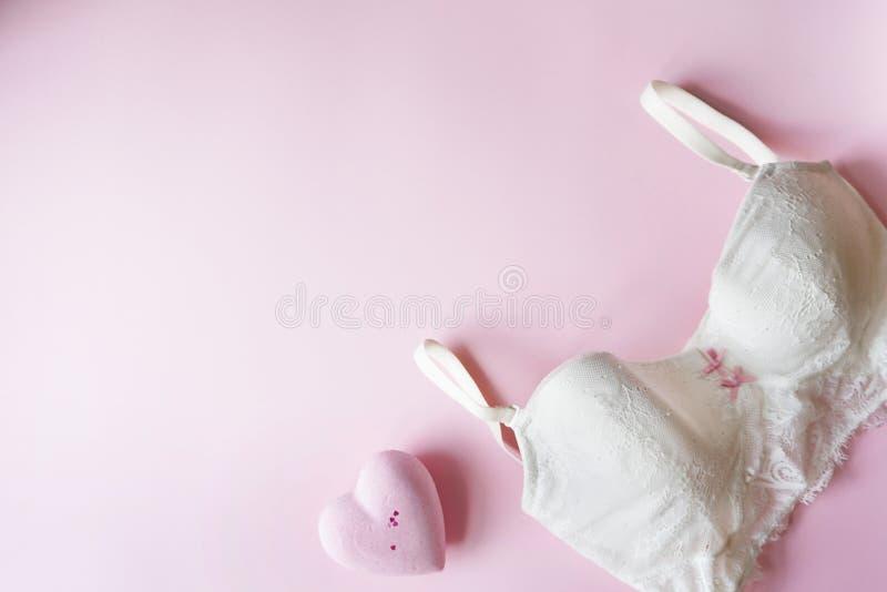 Elegante witte bustehouder, vrouwenondergoed met roze kuuroordhart op roze achtergrond De ruimte van het exemplaar Schoonheid, ma stock fotografie