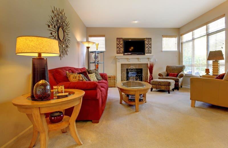 Elegante woonkamer met rode bank, open haard stock afbeelding