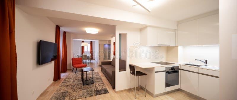 Elegante woonkamer met rode ontwerperleunstoel en moderne witte keuken stock foto's