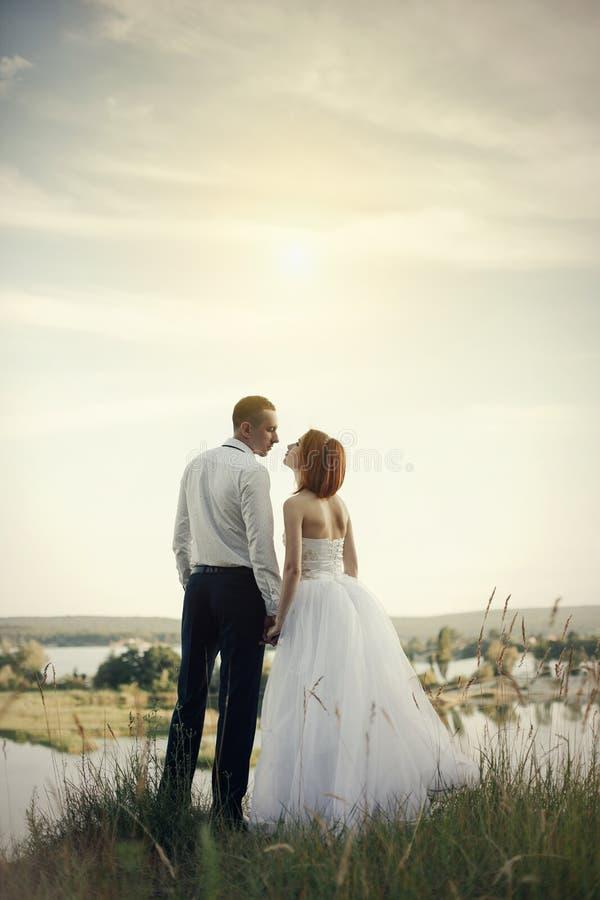 Elegante zachte modieuze bruidegom en bruid dichtbij rivier of meer Het paar van het huwelijk in liefde stock afbeelding