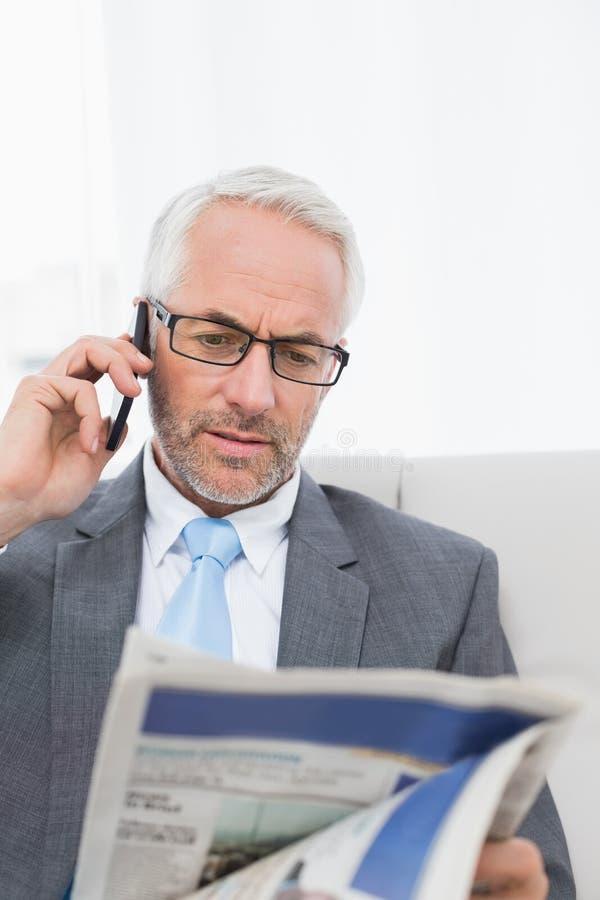 Elegante zakenman die cellphone gebruiken terwijl het lezen van krant royalty-vrije stock foto