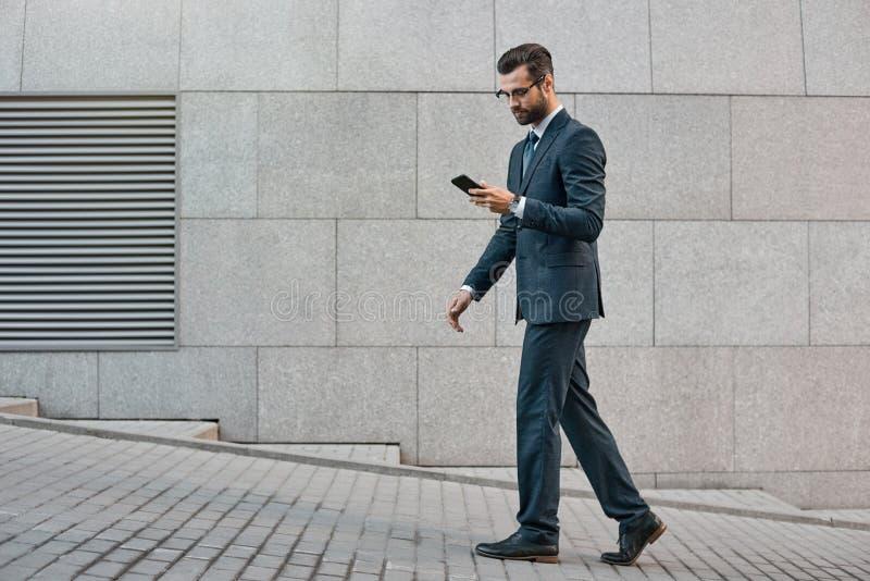 Elegante zakenmanhand die en een smartphone in openlucht houden met behulp van stock foto