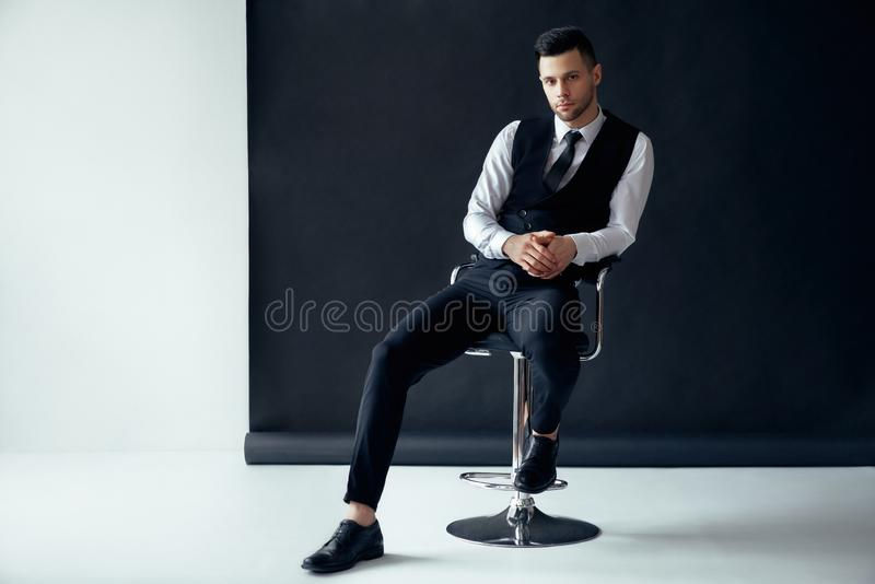 Elegante zekere mens die en op stoel op zwart-witte achtergrond stellen zitten royalty-vrije stock afbeeldingen