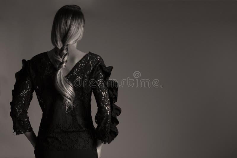 Elegante zwarte uitrusting voor vrouwen in studio, moderne coiffuree stock afbeelding