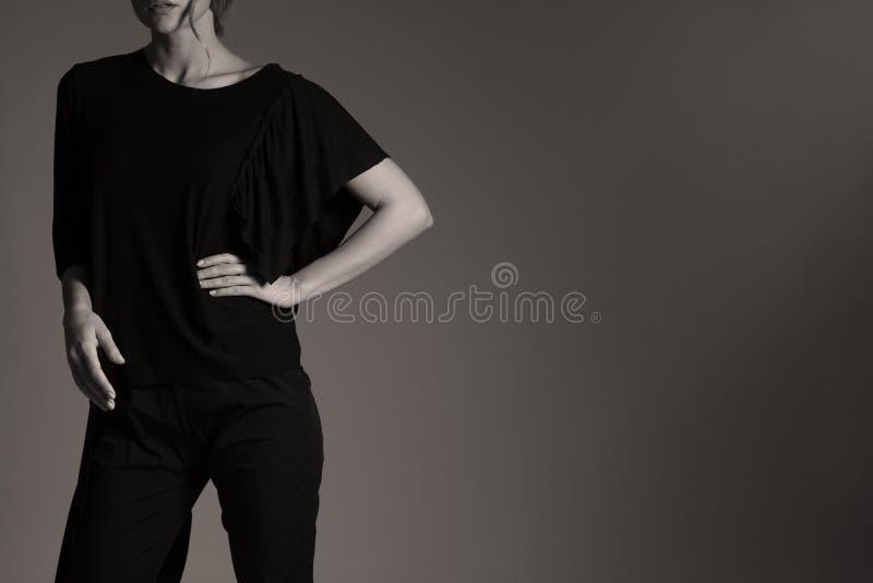 Elegante zwarte uitrusting voor vrouwen in studio, moderne coiffuree royalty-vrije stock afbeelding