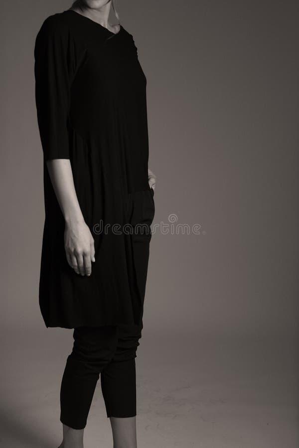 Elegante zwarte uitrusting voor vrouwen in studio, moderne coiffuree stock afbeeldingen