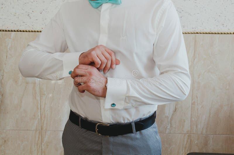 Eleganter Bräutigam knöpft die hellblauen Manschettenknöpfe auf seinem weißen Hemd Tiffany-Farbfliege Karierte graue Klage und ei stockfotografie