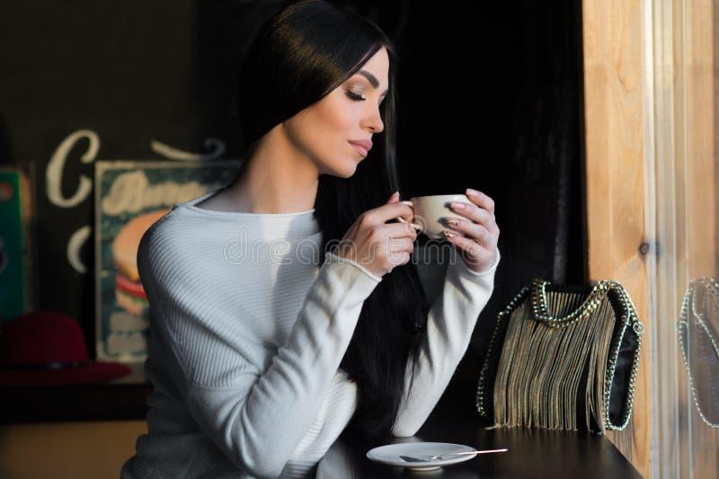 Eleganter Brunette mit Tasse Kaffee lizenzfreie stockfotografie