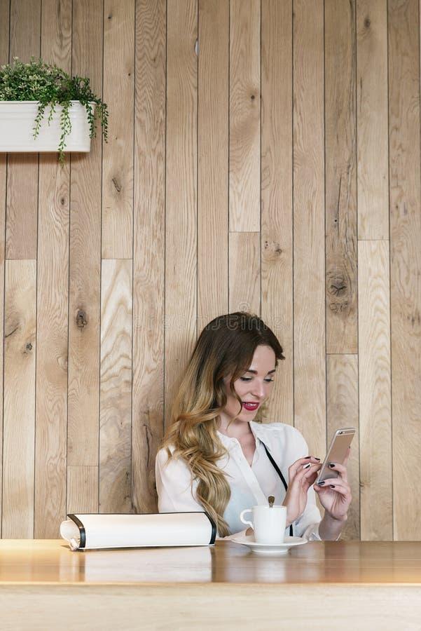 Eleganter Geschäftsfrauschreibenstext mit einem Smartphone in einem restau stockfotografie