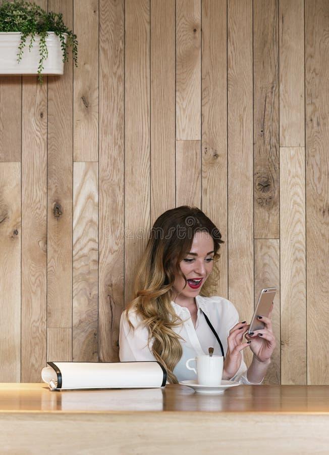 Eleganter Geschäftsfrauschreibenstext mit einem Smartphone in einem restau lizenzfreie stockfotografie