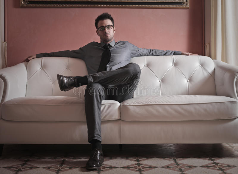 Eleganter Geschäftsmann auf einem Sofa lizenzfreie stockbilder